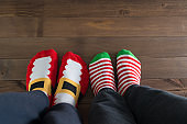 couple withchristmas socks sitting on wooden floor, winter cosy scene
