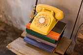 Old yellow rotary phone on the book