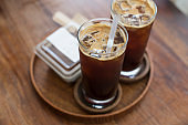 Two iced coffee with glass cups on wooden tray in a coffee shop.