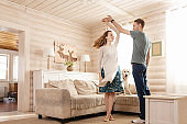 Happy married couple are dancing their new living room along with their beloved dog