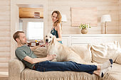 Happy family couple young girl and cute guy spends time sitting with his beloved dog in the cozy room of his country house