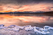Ice on the frozen lake at sunset.