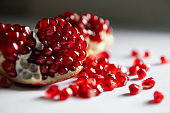 Red ripe pomegranate on the white table close up. Macro image