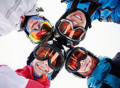 Cheerful friends skiers looking at camera and smiling.