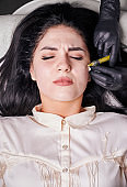 Brunette girl in cosmetology office during plasmolifting procedure lying with closed eyes