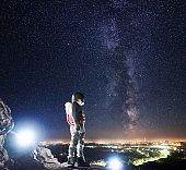 Spaceman standing on rocky mountain under night sky with stars.
