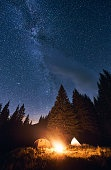 Bright night sky is strewn with stars and Milky Way is visible on it. Evening camping in a pine forest