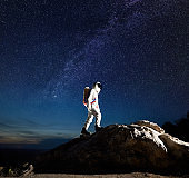 Spaceman walking up the rocky hill under beautiful starry sky.