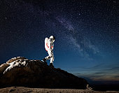 Space traveler walking down the mountain under starry sky.