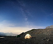 Camp tents in mountains under starry sky.