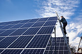 Male electrician installing solar panel under cloudy sky.