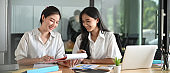 Office women are working together at the wooden working desk over a meeting room as a background.