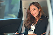 Photo of young beautiful passenger holding a coffee cup and stylus pen in hand while sitting at passenger seat in comfortable car as background. Concept of working during transportation.
