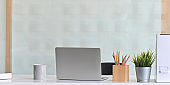 Photo of Computer laptop that putting on white working desk and surrounded by coffee cup, document file, wooden pencil holder and potted plant. Orderly workspace concept.
