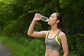 Beautiful women resting and drinking water after doing exercises in park.