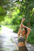 Fitness female doing warmup exercise at the park in the morning.