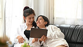Lesbian couple are relaxing with a computer tablet while sitting together on the sofa.