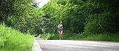Athletic female out jogging through fresh green spring countryside  in a healthy lifestyle concept.