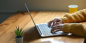 A woman's hands using a white blank screen computer laptop at the wooden working desk.