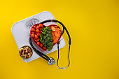 Vegetables in a heart bowl with yellow background