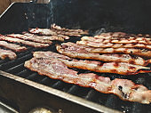 Bacon Cooking on Barbecue Grill