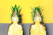 Yellow, gray colors of the year 2021. Trendy wallpaper background concept with two half pineapples