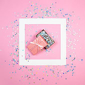 Square empty frame, pink gift box with bibbon full of holographic stars confetti. Minimal flat lay