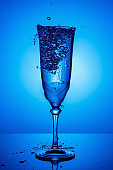 Frozen water jet with splashes and flying water drops in full champagne glass on a thin high leg with reflection on a glossy surface in blue backlight. Stop motion photography