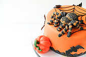 Halloween orange cake decorated with pumpkin, spider, bat and cobweb on a white background