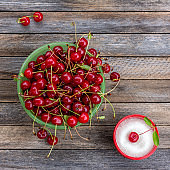 Green bowl with ripe cherry berries and cup with sugar on a wooden background, close up top view