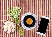 black cup of coffee with milk on a saucer, marshmallow, a bouquet of lily of the valley flowers and a smartphone on the table, top view flat lay