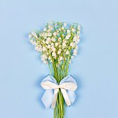 Bouquet of fragrant Lily-of-the-valley flowers with a white and blue bow on a blue background close-up, top view