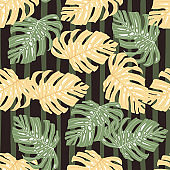 Random seamless pattern with orange and green colored monstera leaf. Dark striped background.