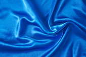 Blue silk background with a folds.  Abstract texture of rippled satin surface