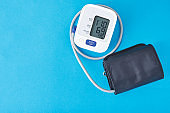 Digital blood pressure monitor on a blue background, closeup. Helathcare and medical concept