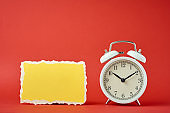 White vintage classic alarm clock with bells and empty torn paper sheet on the red background.  Design blank for time concept