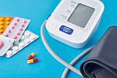 Digital blood pressure monitor and medical pills on a blue background. Healthcare and medicine concept