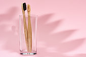Bamboo toothbrushes in the glass and leaf shadows on pink background
