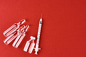 Syringes and medicine bottles with medication on a red background, top view with copy space