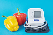 Digital blood pressure monitor and fresh vegetables pepper on a blue background. Healthcare concept