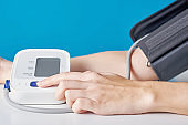 Woman measuring blood pressure with a digital pressure monitor against blue background. Health care and medical concept