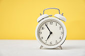 Time concept. White retro alarm clock on yellow background with copy space. Time concept