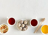 Homemade raw candy energy balls with almond, cashews, peanut butter and hazelnuts on the plate with tea cups flat lay on gray background with copy space. Organic snack. Vegetarian food.