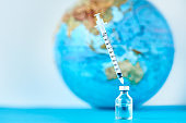 Medical syringe and ampoule with a medicine against Earth globe. Virus threat and epidemic protection concept
