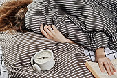 Sleeping woman covered under blanket in bed and vintage alarm clock on pillow. Lazy morning ana wake up concept