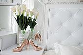 Elegant white wedding shoes at bride morning.