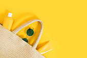 Summer yellow bright flatlay on colorful background with wicker straw bag, tubes and bottle with sunscreen, green sunglasses. Hard shadows and light. Top view. Flat lay. Trend style. Copyspace.
