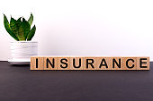 Insurance word concept written on wooden cubes on a dark table with flower and light background