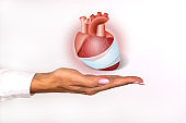 Protect health, healthcare and prevention of heart problems, cardiology concept. Female hand holds a symbol of a sick heart.