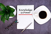 Knowledge is power is written in a notebook lying on a grey table with a pen and glasses.